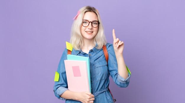 Молодая красивая женщина-альбинос улыбается и выглядит дружелюбно, показывая номер один. студенческая концепция