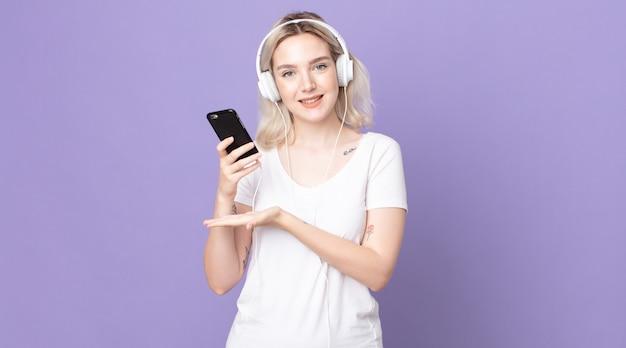 Молодая красивая женщина-альбинос весело улыбается, чувствует себя счастливой и демонстрирует концепцию в наушниках и смартфоне