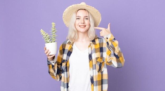 自信を持って笑顔の若いかわいいアルビノの女性は、自分の広い笑顔を指して、観葉植物のサボテンを持っています