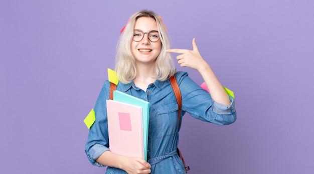 自信を持って笑顔の若いかわいいアルビノの女性は、自分の広い笑顔を指しています。学生の概念