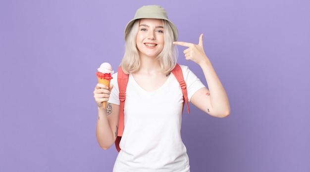 自信を持って笑顔の若いかわいいアルビノの女性が自分の広い笑顔を指しています。夏のコンセプト