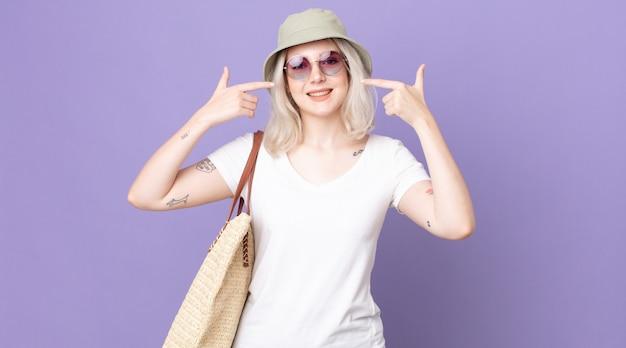 自信を持って笑顔の若いかわいいアルビノの女性は、自分の広い笑顔を指しています。夏のコンセプト