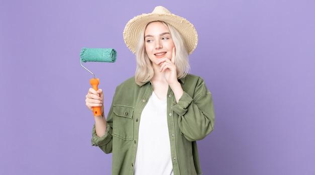 Молодая красивая женщина-альбинос счастливо улыбается, мечтает или сомневается и держит в руках валик