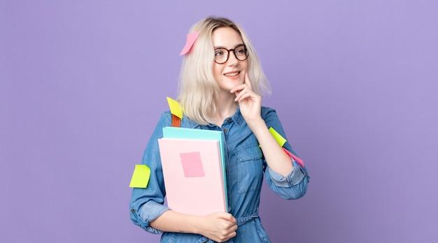 Молодая красивая женщина-альбинос счастливо улыбается и мечтает или сомневается. студенческая концепция