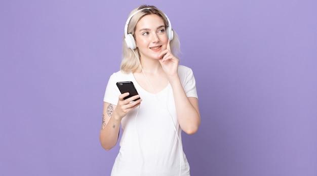 Молодая красивая женщина-альбинос счастливо улыбается и мечтает или сомневается в наушниках и смартфоне