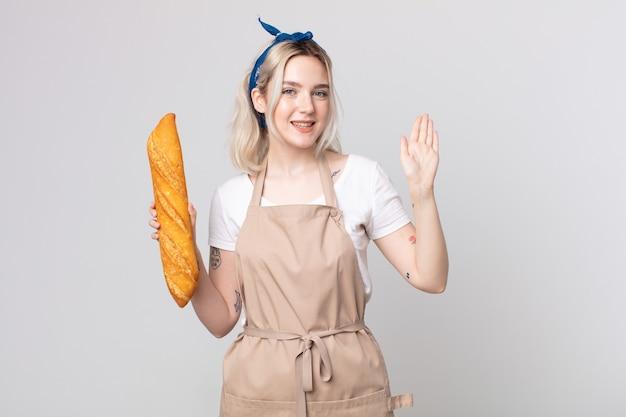 젊고 예쁜 알비노 여성은 행복하게 웃고, 손을 흔들며, 빵 바게트로 당신을 환영하고 인사합니다