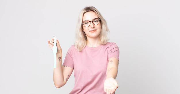 Молодая красивая женщина-альбинос счастливо улыбается, дружелюбно предлагает и показывает концепцию, держащую часы с часами