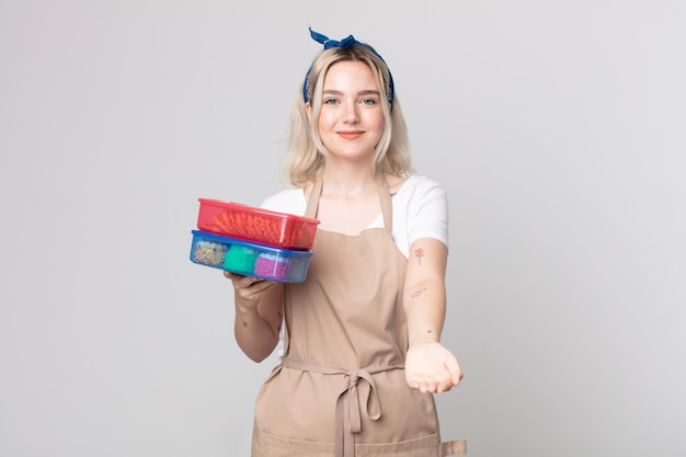 フレンドリーで幸せそうに笑って、食べ物のタッパーウェアを保持しているコンセプトを提供し、示している若いかわいいアルビノの女性