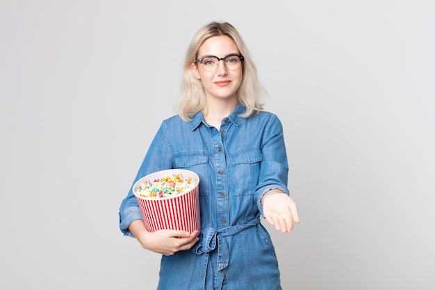 Young pretty albino woman smiling happily with friendly and  offering and showing a concept with a pop corns bucket