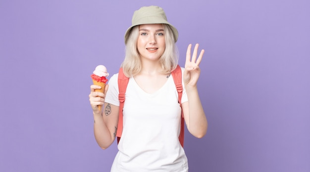 Young pretty albino woman smiling and looking friendly, showing number three .summer concept