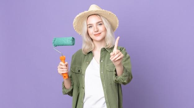 Молодая симпатичная женщина-альбинос гордо и уверенно улыбается, делая номер один и держа валик с краской