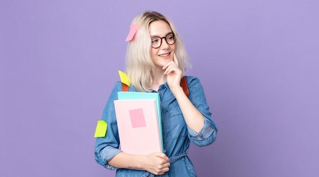 Молодая красивая женщина-альбинос улыбается с счастливым, уверенным выражением лица, положив руку на подбородок. студенческая концепция