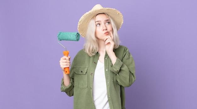 Молодая симпатичная женщина-альбинос думает, чувствует себя неуверенно и смущенно и держит валик с краской