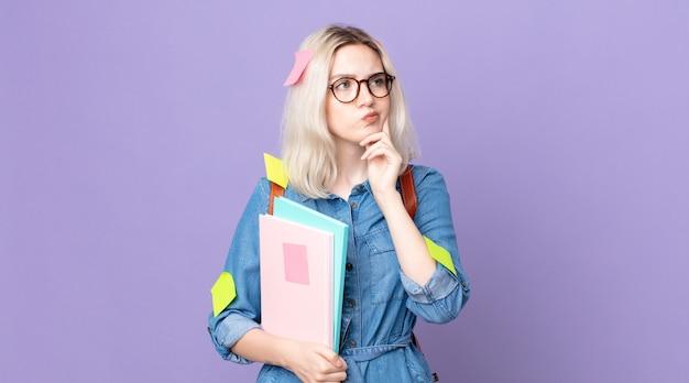 Молодая красивая женщина-альбинос думает, сомневается и смущается. студенческая концепция