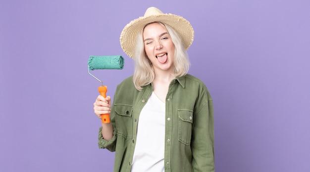쾌활하고 반항적인 태도를 가진 젊고 예쁜 알비노 여성, 농담을 하고 혀를 내밀고 롤러 페인트를 들고