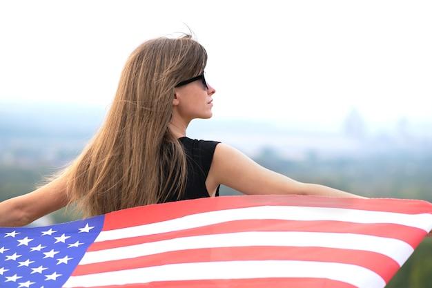 긴 머리를 가진 젊고 예쁜 미국 여성이 바람에 미국 국기를 들고 야외에서 따뜻한 여름날을 즐기고 있습니다.