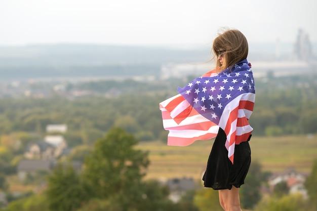 Молодая красивая американская женщина с длинными волосами, держащая размахивая на ветру флаг сша на ее плечах, стоя на открытом воздухе, наслаждаясь теплым летним днем.