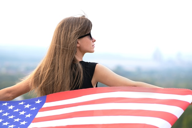 Young pretty american woman with long hair holding waving on wind usa  flag on her sholders standing outdoors enjoying warm summer day.