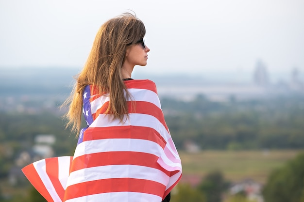Young pretty american woman with long hair holding waving on wind usa  flag