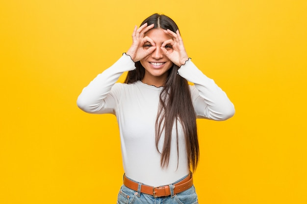 Young pretty arab woman against a yellow  showing okay sign over eyes