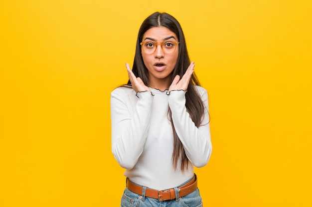 Young pretty arab woman against yellow  surprised and shocked.