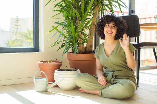 じょうろと植物を持つ、自宅で若いかなりアラブの女性