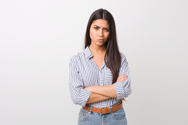 Young pretty arab woman frowning face in displeasure, keeps arms folded.