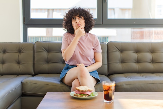 Young pretty arab woman having a sandwich sitting on a sofa at home