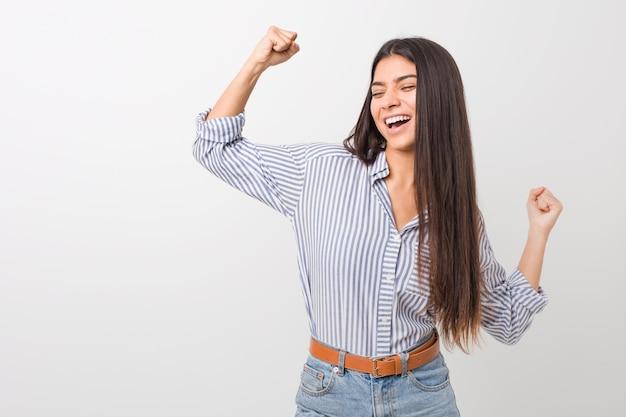 Молодая красивая арабская женщина поднимая кулак после победы, концепции победителя.