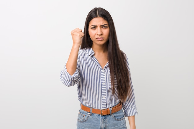 Young pretty arab woman showing fist to camera, aggressive facial expression.