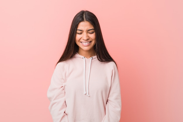Young pretty arab woman wearing a casual sport look laughs and closes eyes, feels relaxed and happy.
