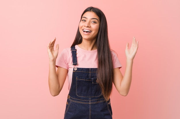Young pretty arab woman wearing a jeans dungaree celebrating a victory or success