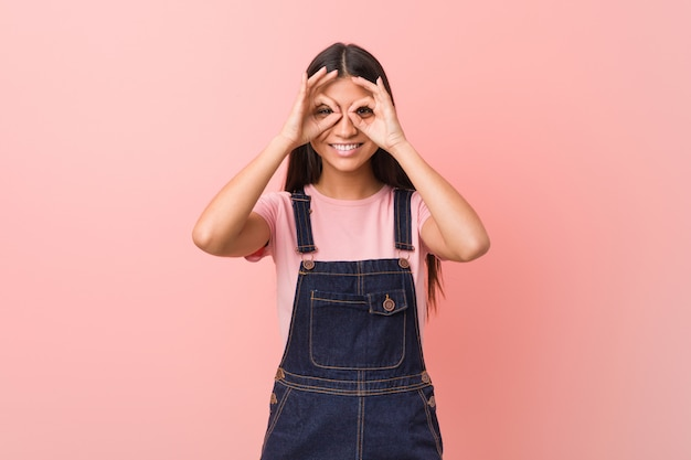 Young pretty arab woman wearing a jeans dungaree showing okay sign over eyes