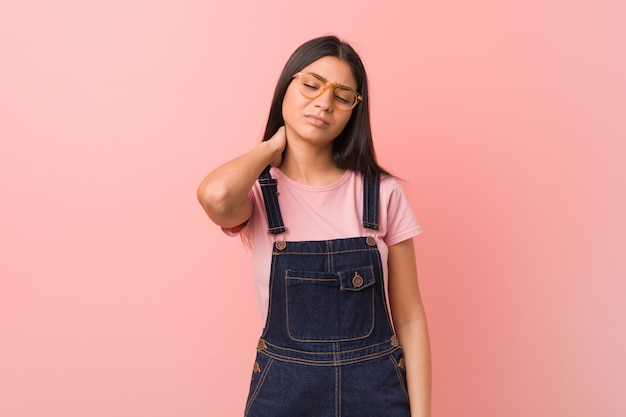 Young pretty arab woman wearing a jeans dungaree suffering neck pain due to sedentary lifestyle.