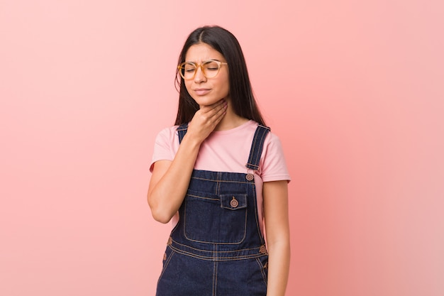 Young pretty arab woman wearing a jeans dungaree suffers pain in throat