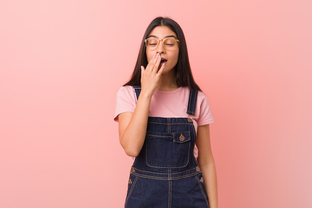 Young pretty arab woman wearing a jeans dungaree yawning showing a tired gesture covering mouth with hand.