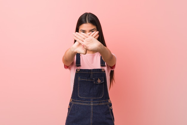 Young pretty arabic woman wearing a jeans dungaree doing a denial gesture