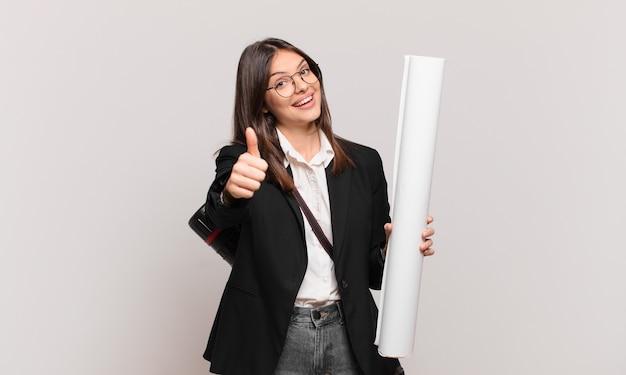 Молодая красивая женщина-архитектор чувствует себя гордой, беззаботной, уверенной и счастливой, позитивно улыбается с большими пальцами руки вверх