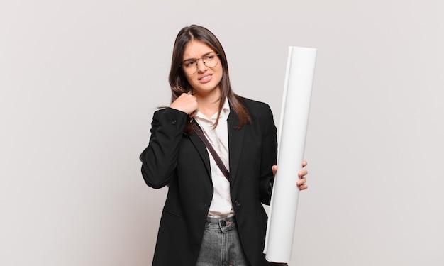 Молодая симпатичная женщина-архитектор чувствует стресс, тревогу, усталость и разочарование, тянет за шею рубашки и выглядит разочарованной проблемой