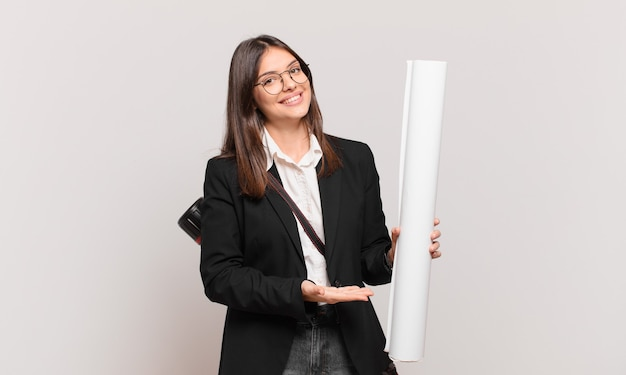 Young pretty architect woman smiling cheerfully, feeling happy and showing a concept in copy space with palm of hand