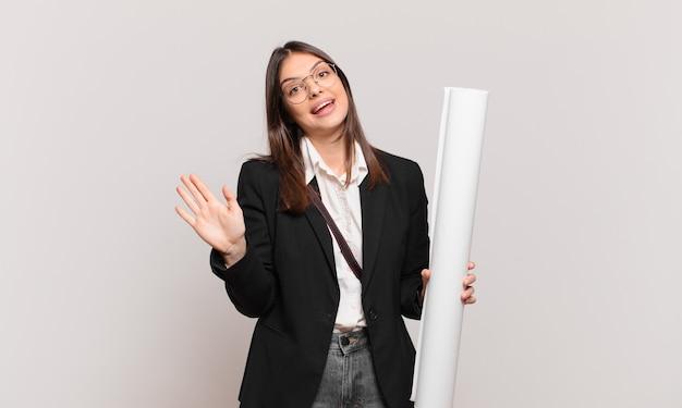 若くてかわいい建築家の女性が幸せにそして元気に笑って、手を振って、あなたを歓迎して挨拶するか、さようならを言っています