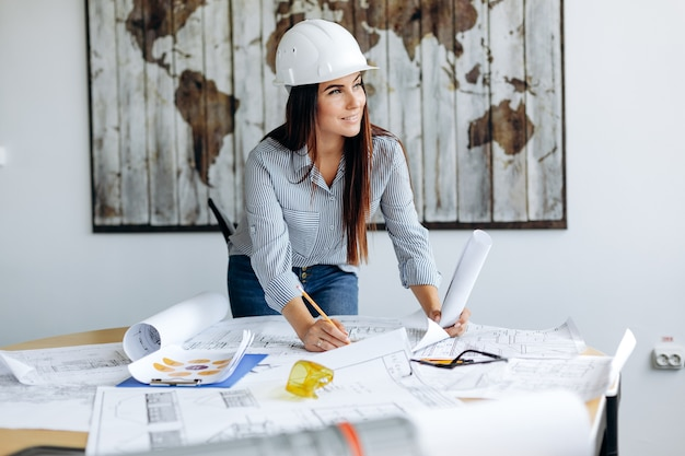 Young pretty architect woman working in the office