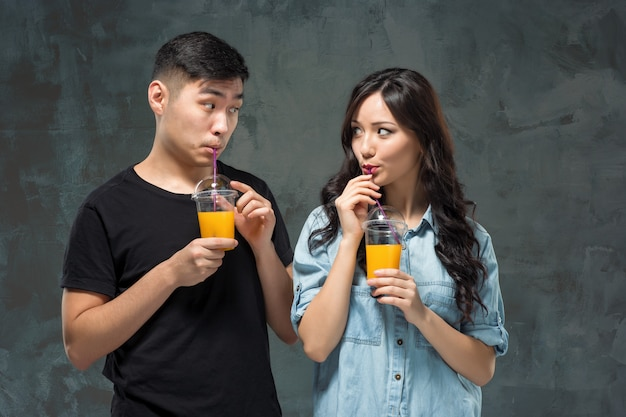 A young pretty asian couple with a glasses of orange juice