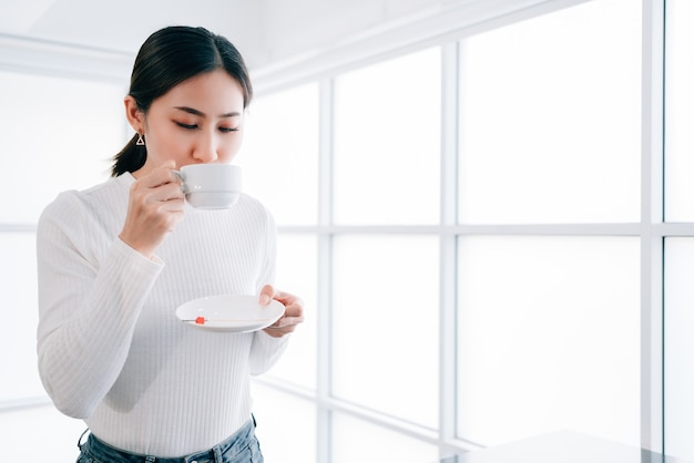 A young pretty asian female wearing a sweater drinking a cup of hot coffee.