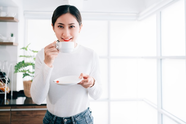 A young pretty asian female wearing a sweater drinking a hot coffee with a smile.