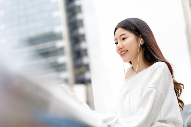 Young pretty asian girl listening to music on earphones in the city