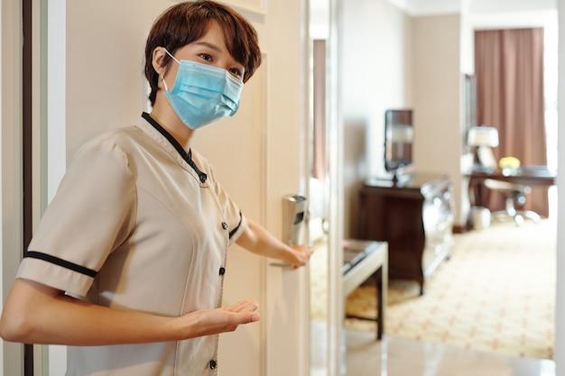 ホテルの部屋のドアを開けて、中にゲストを招待する若いかわいいアジアのホテルマネージャー