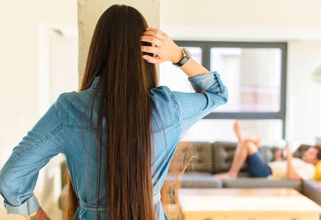 Молодая симпатичная азиатская женщина чувствует себя невежественной и запутанной, думая о решении, с рукой на бедре и другой на голове, вид сзади