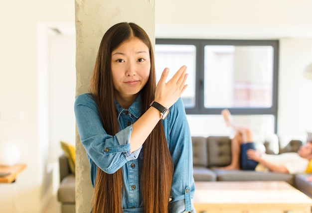 Young pretty asian woman feeling confused and clueless, wondering about a doubtful explanation or thought