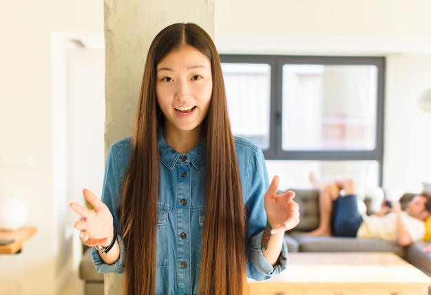 Молодая симпатичная азиатская женщина чувствует себя счастливой, удивленной, удачливой и удивленной, как будто серьезно говорит: «боже»? невероятно